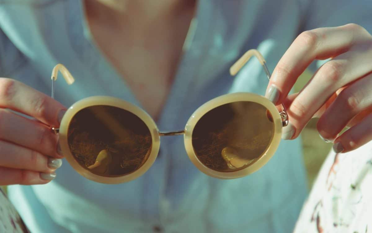 woman holding prescription sunglasses