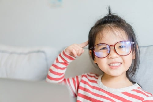 child wearing glasses and pointing to brain